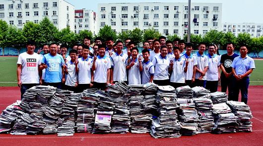 """青岛63中学生捐赠的报纸在操场上堆成了""""小山""""."""