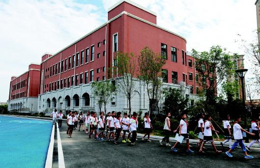 青岛滨海学校里,学生们走在现代化的校园里,新校整体呈砖红色,搭配