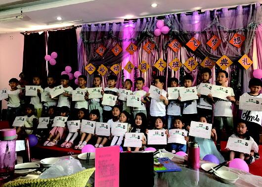 金岭幼儿园的小朋友展示毕业证.